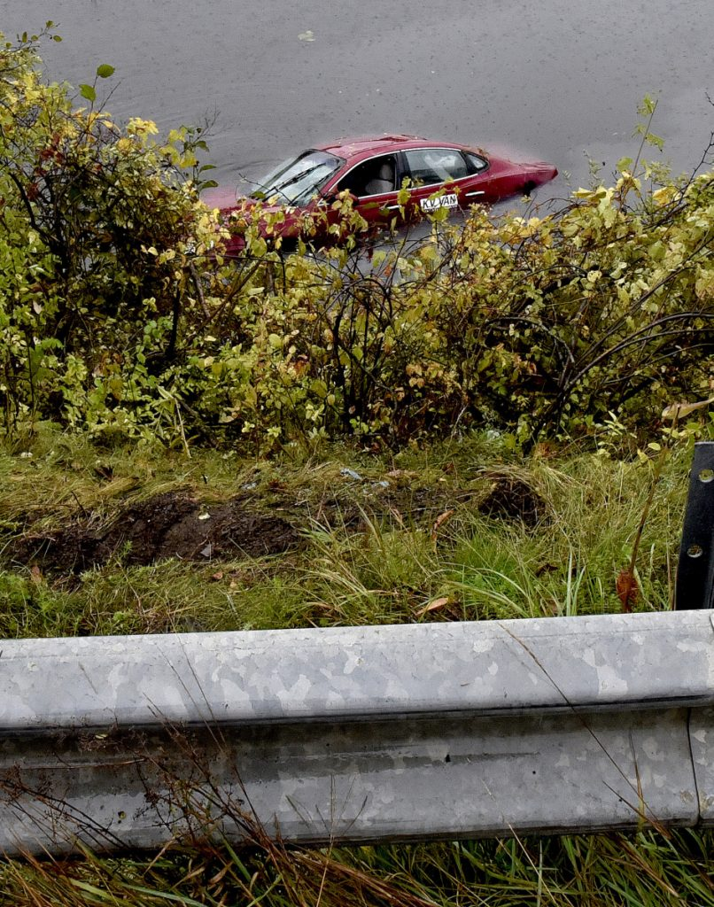 A KV Van transport car stands upright Thursday in a small pond off Middle Road in Fairfield, a short distance from the Back Road intersection, after landing that way that morning. The northbound car rode up and over the guardrail and down an embankment to the water. The driver was taken to a hospital, according to a firefighter.