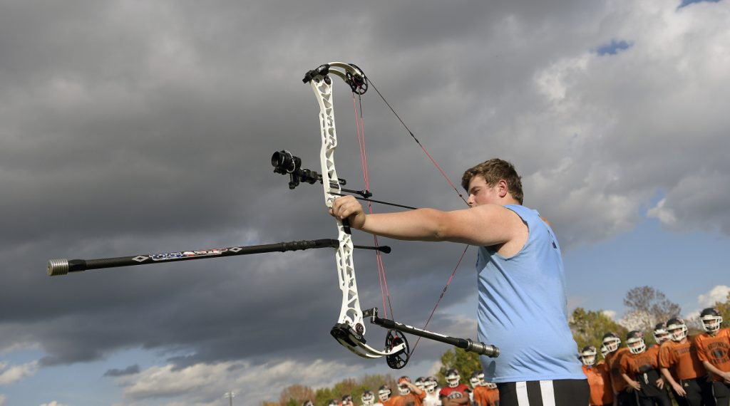 Gardiner Area High School lineman Brad Sandelin draws a bead with his bow before practice Wednesday in Gardiner. The varsity football player is also a world champion archer.