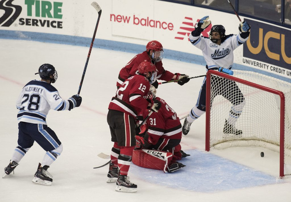 University of Maine's Jack Quinlivan, right, and Adrian Holesinsky, left, celebrate a second period goal by Ryan Smith during a game against St. Lawrence at Alfond Arena in Orono on Friday.