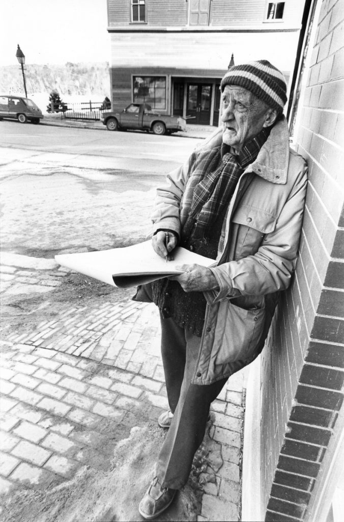 Renowned Hallowell artist Ray Skolfield draws at the corner of Winthrop Street and Water Street in March 1990. The new location of the Harlow Gallery sits in the background. Skolfield's work has been featured in the Smithsonian Art Museum.