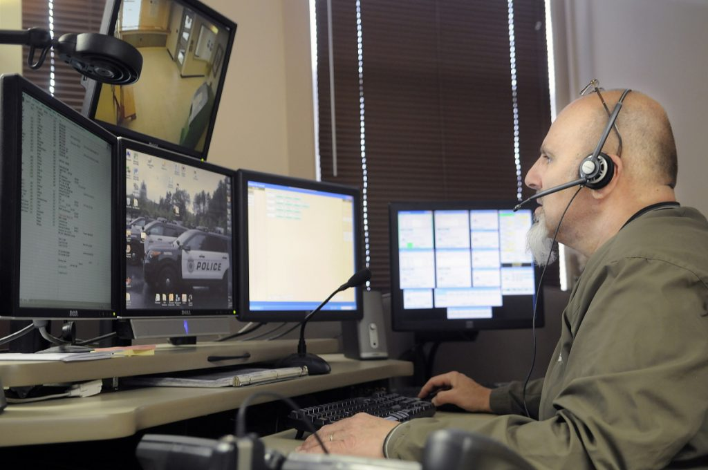 City of Augusta dispatcher Mike Rankins speaks in 2015 with police officers while handling a radio call at the city's emergency communications center.