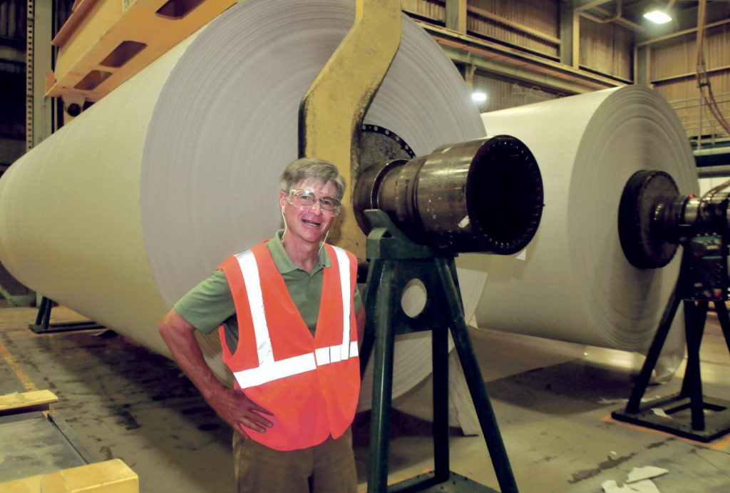 UPM Madison President and CEO Russ Drechsel stands beside two finished rolls of paper in August 2015. The mill closed at the end of May 2016. The paper machine was sold this summer and is being moved to China.