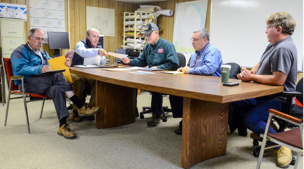 Al Hodson, left, and Mark McCluskey, of A.E. Hodson Consulting Engineers, open bids Sept. 25 for a new Farmingdale fire station and pass them along to committee members — Selectman Wayne Kilgore, Assistant Fire Chief Mike LaPlante and Clerk of the Works Rick Seymour — in the Farmingdale Town Office.