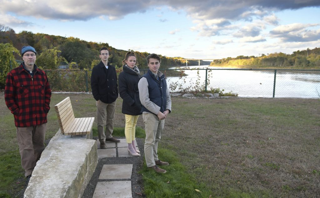 University of Maine at Augusta architecture laboratory supervisor Oliver Solmitz, left, and students, from left, Andrew Treworgy, Shauna Riordan and Sam Gerken, stand on Thursday with the bench they created at Mill Park in Augusta.