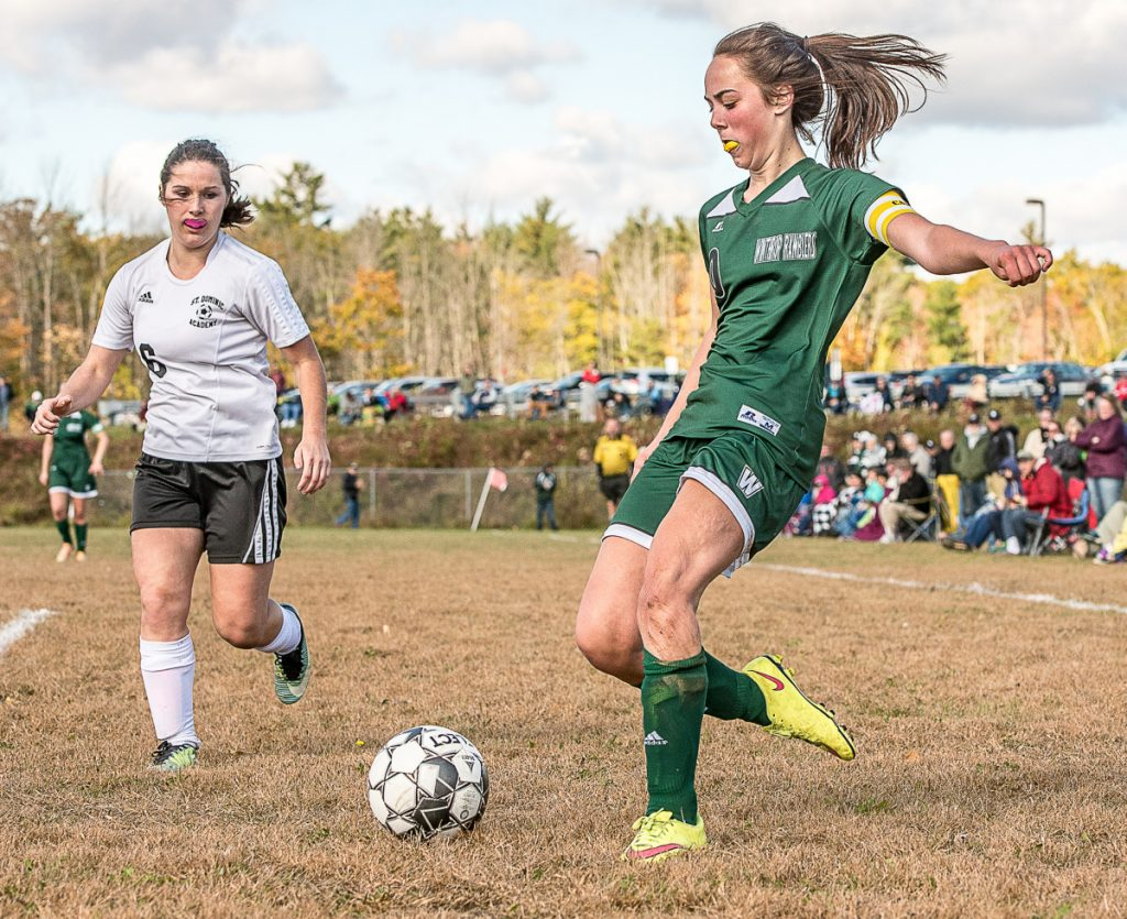 Winthrop's Kena Souza kicks the ball as St. Dominic's Emma Wolverton comes into the play from the left during Saturday's Class C South preliminary game in Winthrop.
