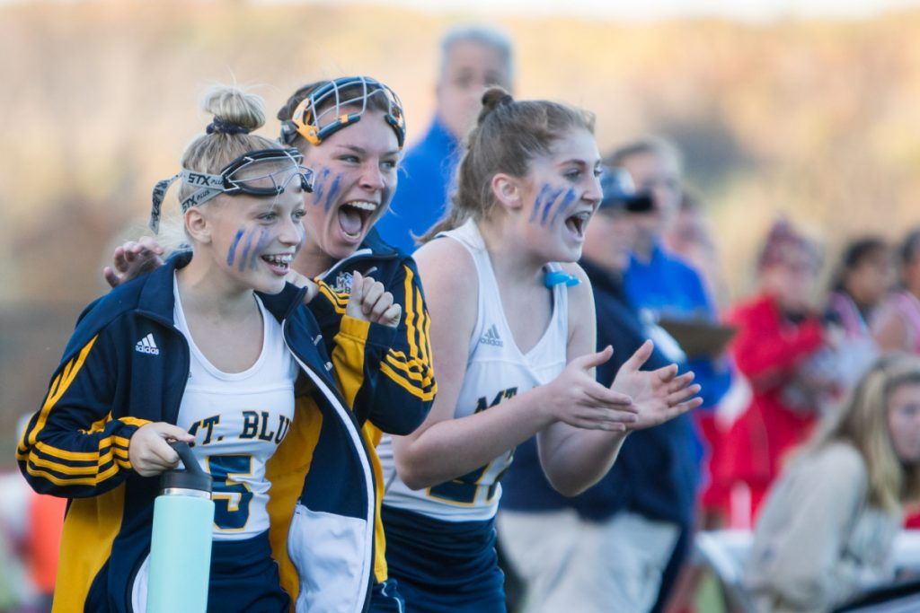 Photo by Jennifer Bechard   Mt. Blue's Farrah Ballou, left, Whitney Fraser, center, and Kelsey Dorman cheer as the Cougars defeated Cony in a Class A North semifinal game Saturday afternoon in Farmington.