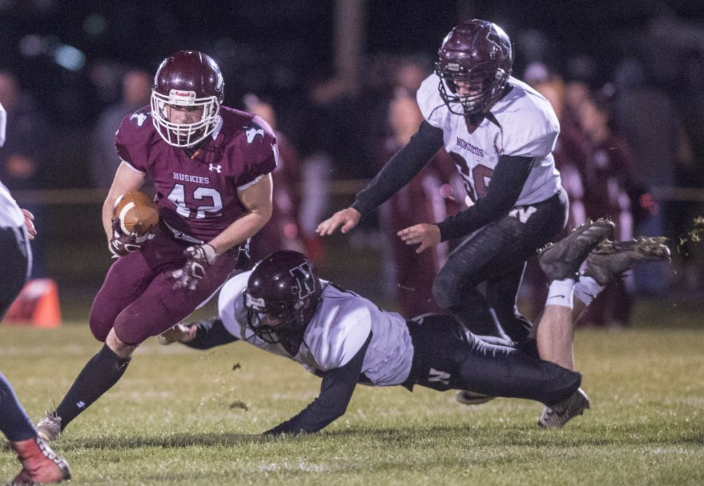 Staff photo by Michael G. Seamans   Maine Central Institute running back Tucker Sharples (42) breaks a tackle and hits a hole in the Nokomis defensive line during a Class C North game Friday night in Pittsfield.