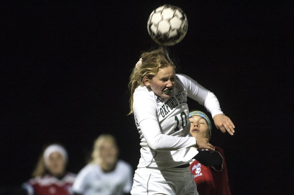 Staff photo by Michael G. Seamans   Oxford Hills' Ceceila Diete Rich heads the ball over Messalonskee players during a Class A North quarterfinal game Tuesday night at Thomas College.