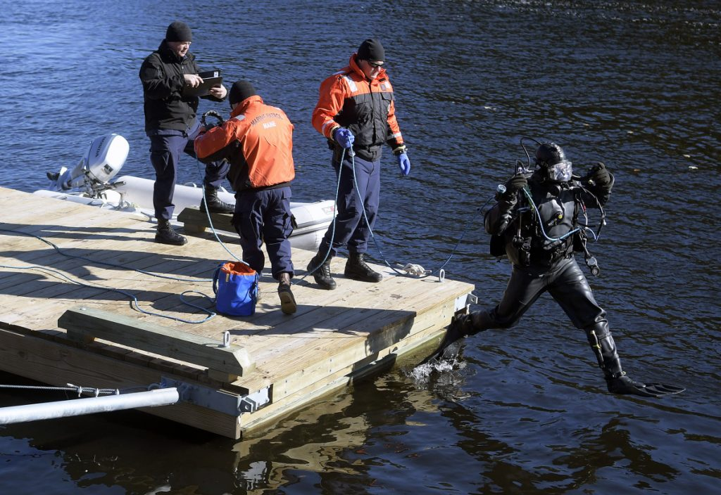 A diver from the Department of Public Safety's dive team leaps off the dock Friday on the Kennebec River in Richmond. Authorities found a body Friday after searching by air, on the water and below the surface for Mark Johnston, 64, who disappeared Thursday night on the river while mooring a boat, police said.