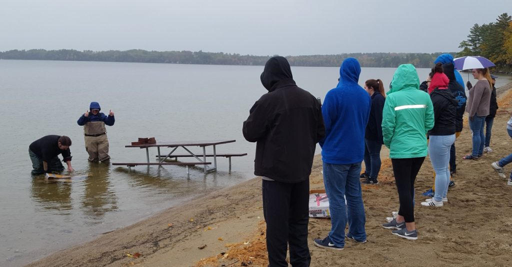 Students from central Maine watch as judges Michael Chamberland, left, and Ellen Benson test the seaworthiness of their homemade boats at JMG's Leadership Education Conference in Rome, Maine.