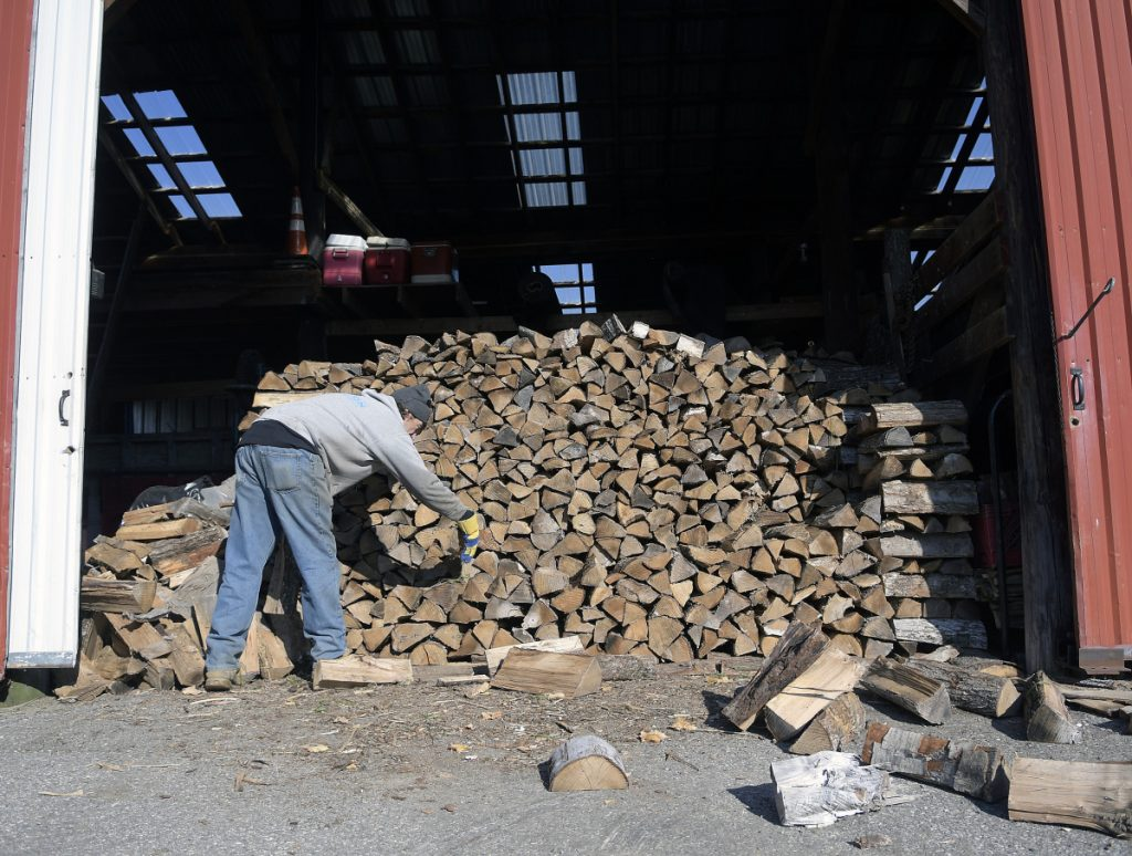 Rick Carmichael stacks firewood Tuesday in a shed at E.C. Barry & Son in Farmingdale. The firewood dealer uses the wood to heat the offices at the business.