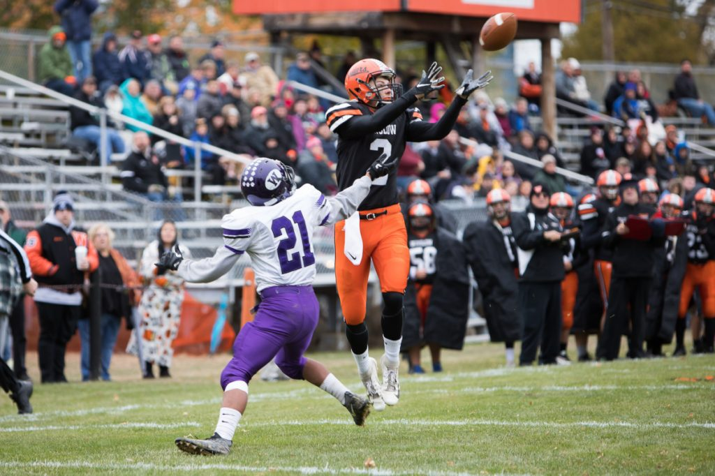Winslow receiver Marek Widerynski catches a touchdown pass in front of Waterville defender Anthony Singh during a Class C North quarterfinal game Saturday in Winslow.