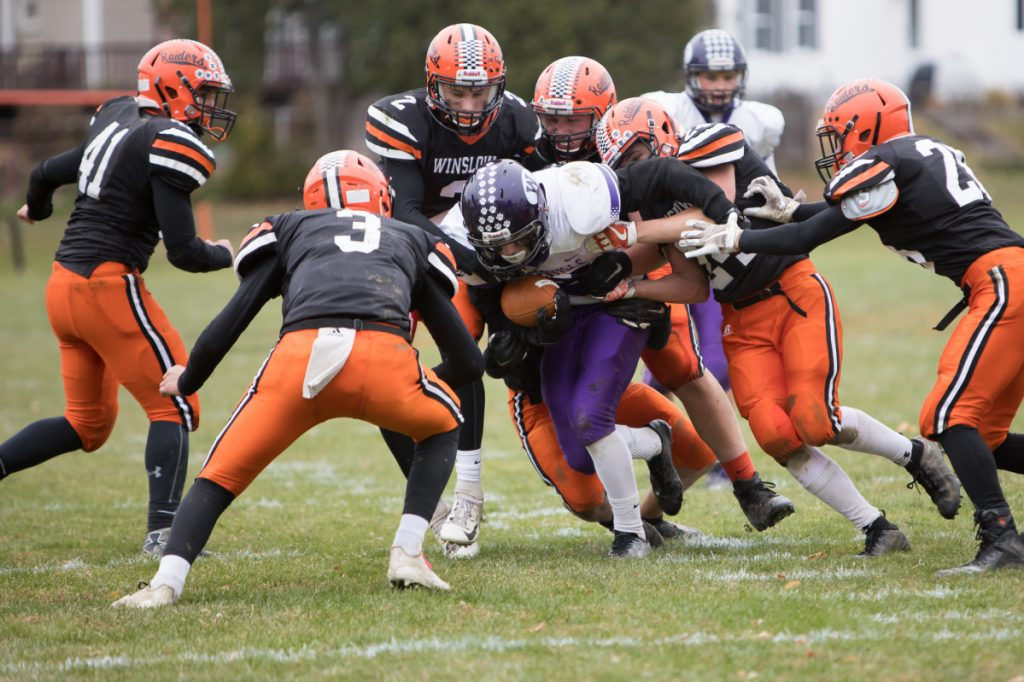Waterville running back Nicholas Wildhaber draws a crowd of Winslow defenders during a Class C North quarterfinal game Saturday in Winslow.