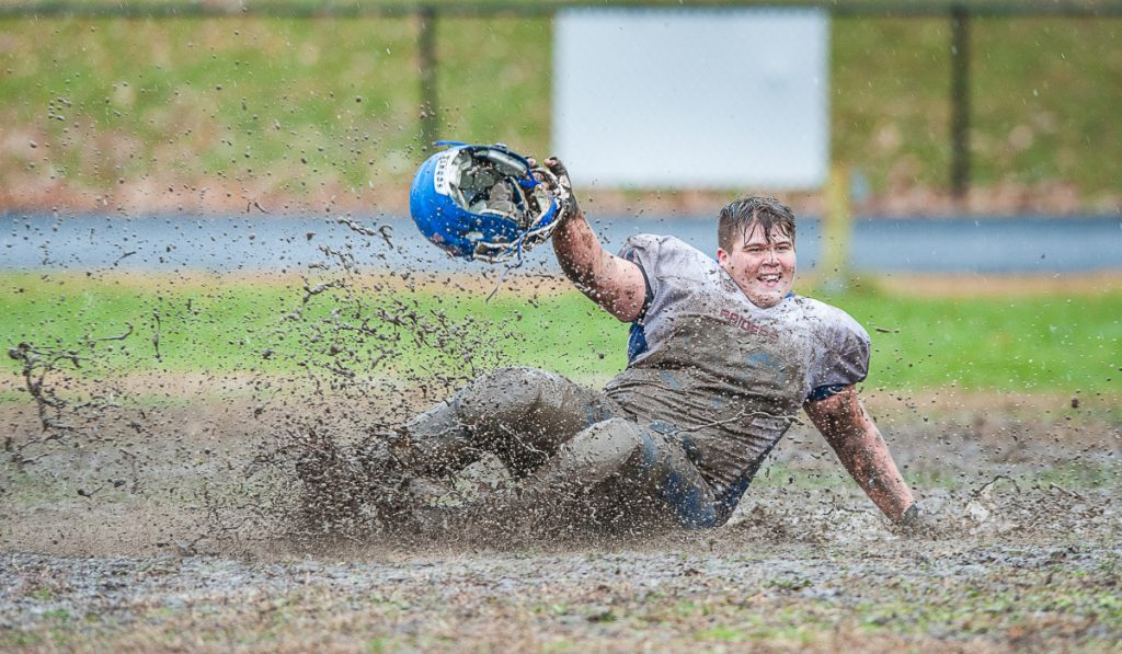 Oak Hill's James Borkowski slides through the mud after the Raiders defeated rival Lisbon in overtime in the Class C South quarterfinals Saturday in Lisbon.