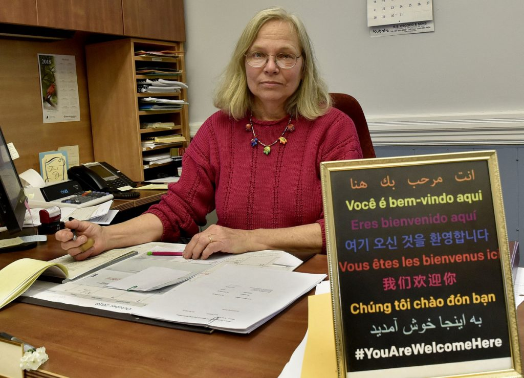 "Franklin County Treasurer Pamela Prodon, at her desk at the Franklin County Courthouse in Farmington on Monday, displays a sign on her desk that states ""You Are Welcome Here"" in nine languages similar to the signs displayed by residents, including her in-laws, near the Tree of Life synagogue in Pittsburgh where a gunman killed 11 worshipers on Saturday."