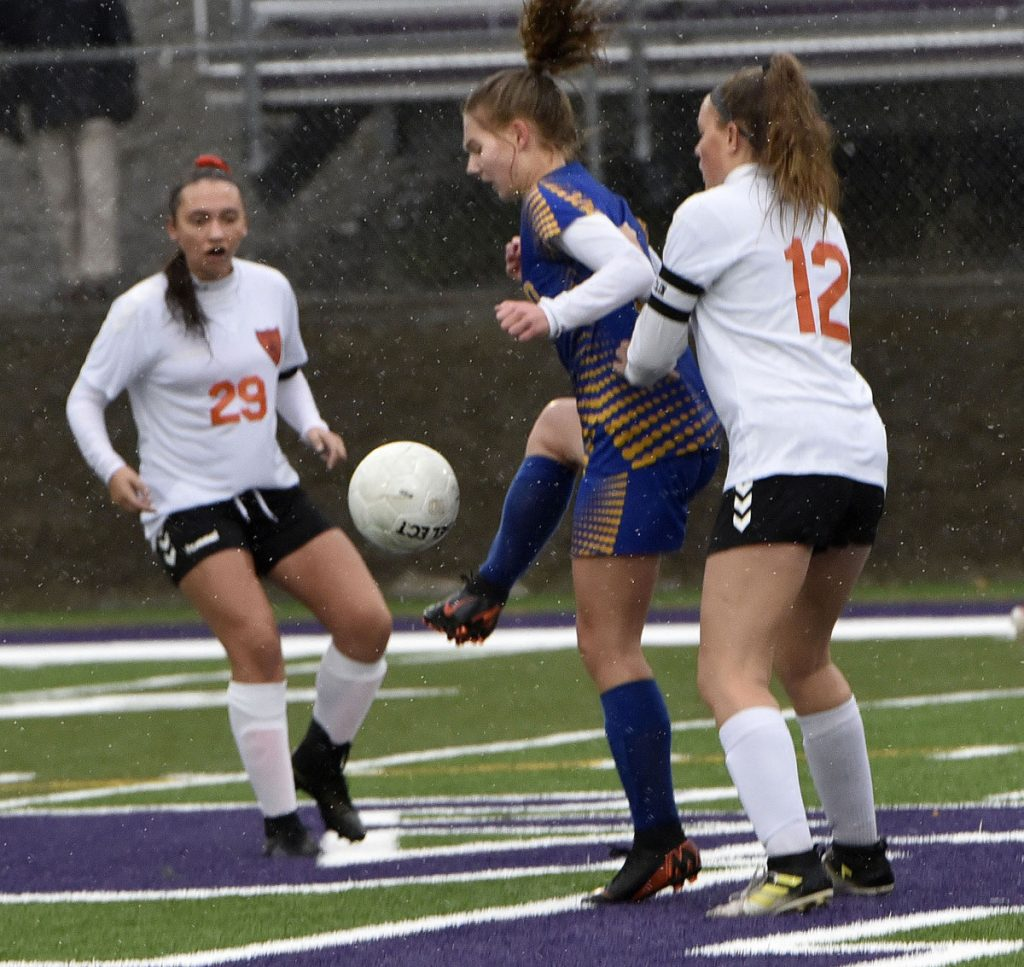 Winslow's Desiree Veilleux, left, and Paige Trask pressure Hermon's Sydney Gallop during a Class B North semifinal against Hermon on Monday at Hampden Academy.