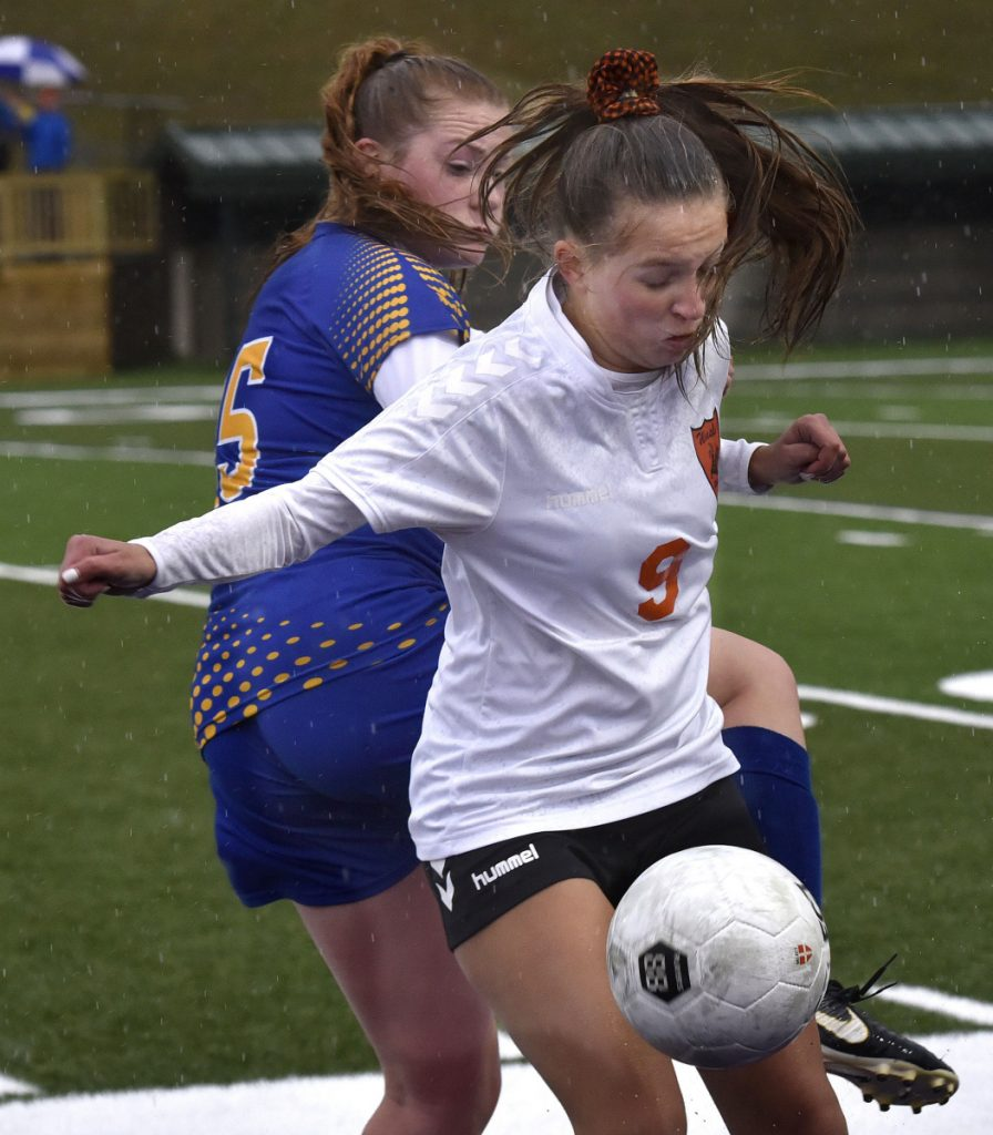 Winslow's Alison Stabins, front, reaches tries to fend off  Hermon's Emily Smith during a Class B North semifinal against Hermon on Monday at Hampden Academy.