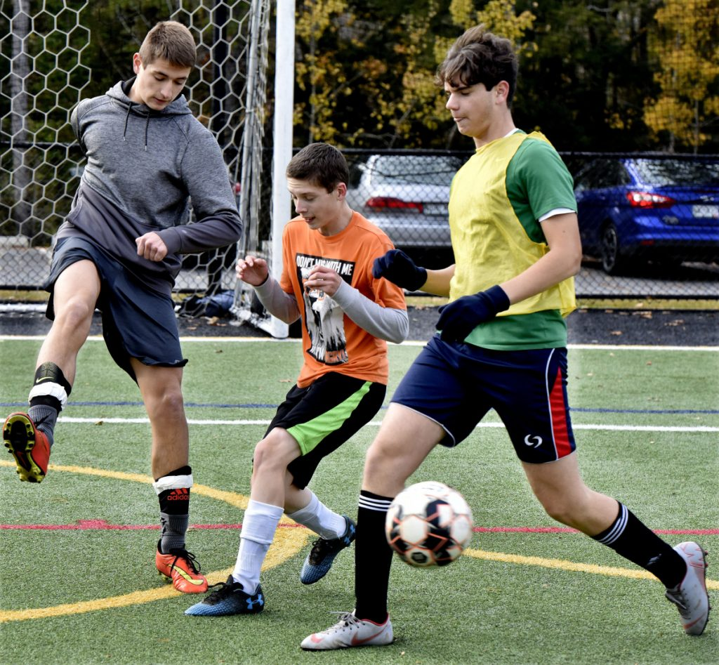 Temple Academy soccer players from left, Steve Kruta, Noah Young and Gian Marco Rossi compete in practice Tuesday in Waterville. The team will play today in the regional final game against North Yarmouth Academy.