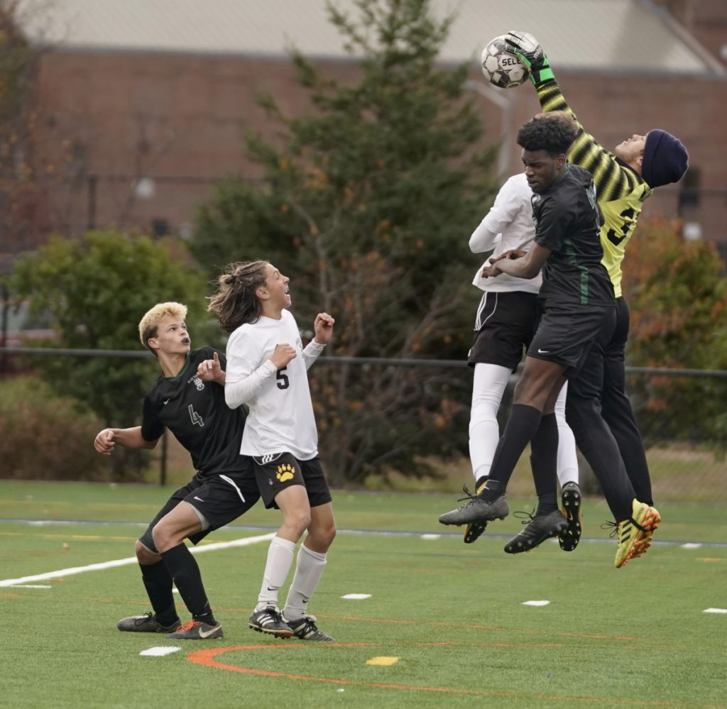 Maranacook keeper Ryan Worster grabs the ball before Diraige Dahia of Waynflete can get his head on it during the Class C South regional final Wednesday in Portland. At left is Oliver Burdick of Waynflete and Carter McPhedran of Maranacook.