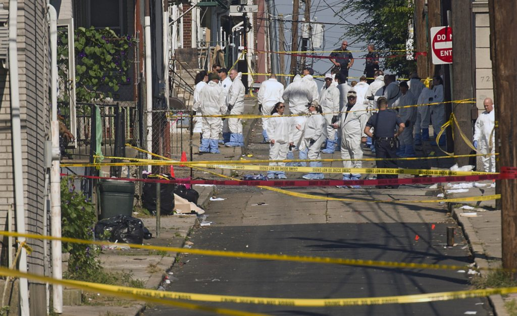 Federal and local authorities investigate along North Hall Street in Allentown, Pa., on Sunday after a fiery car explosion rocked the neighborhood, killing three males on Saturday night.