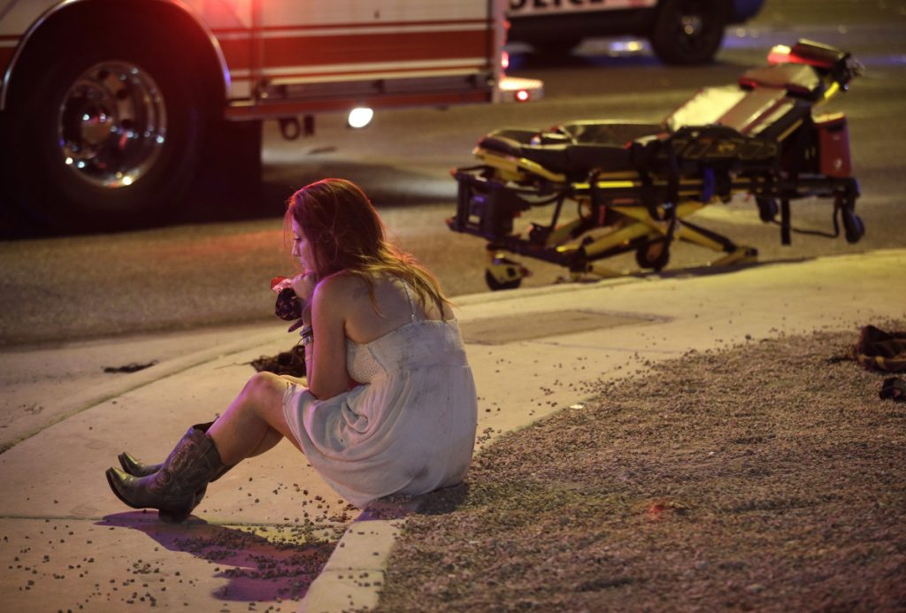 A woman sits on a curb at the scene of a shooting outside a music festival on the Las Vegas Strip on Oct. 2, 2017. It took 11 minutes for the gunman in the deadliest mass shooting in modern U.S. history to kill 58 people. Then he killed himself. A year later, Las Vegas police and the FBI have still found no motive for the rampage.