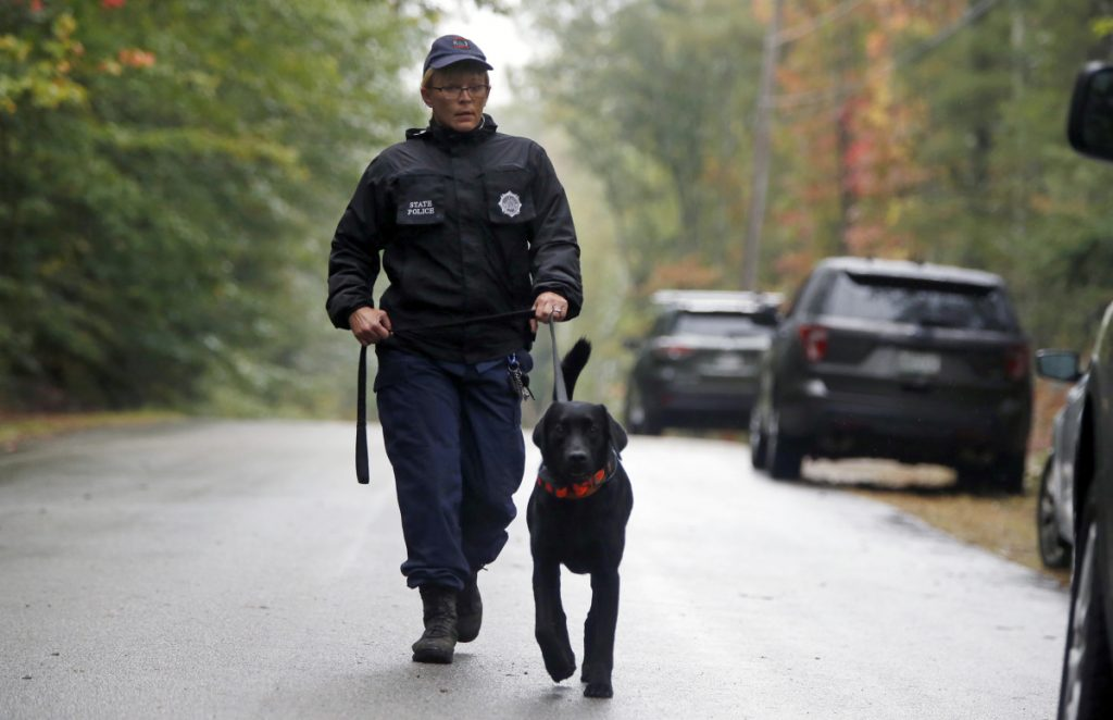 A Maine State Trooper on Tuesday leads a search dog toward the Lufkin Road home of Kristin Westra in North Yarmouth. Police say it's still too soon to characterize the disappearance as suspicious.