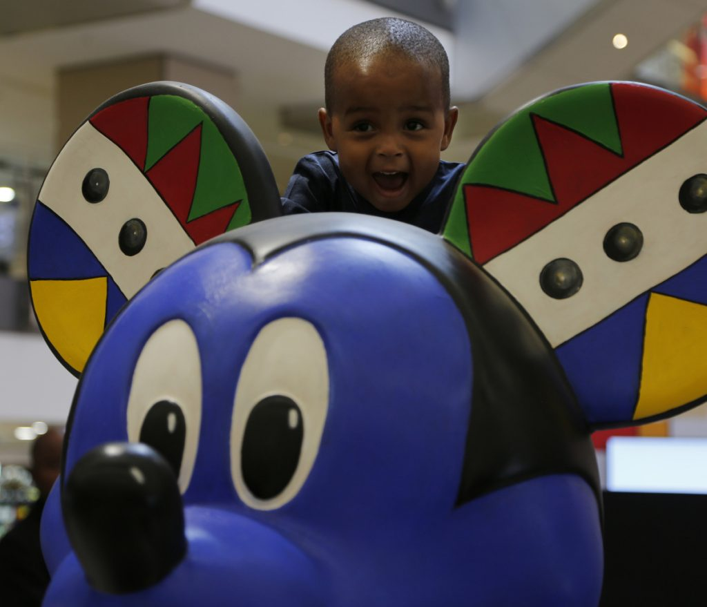 A child looks over the head of a Mickey Mouse statue at an exhibition at Sandton City in Sandton, South Africa, Sunday.