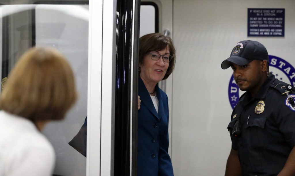 Sen. Susan Collins, R-Maine, responds to a reporter's question Wednesday as she is accompanied by a Capitol Police officer. The corridors outside her office were kept clear by police Wednesday, apparently because of security concerns.