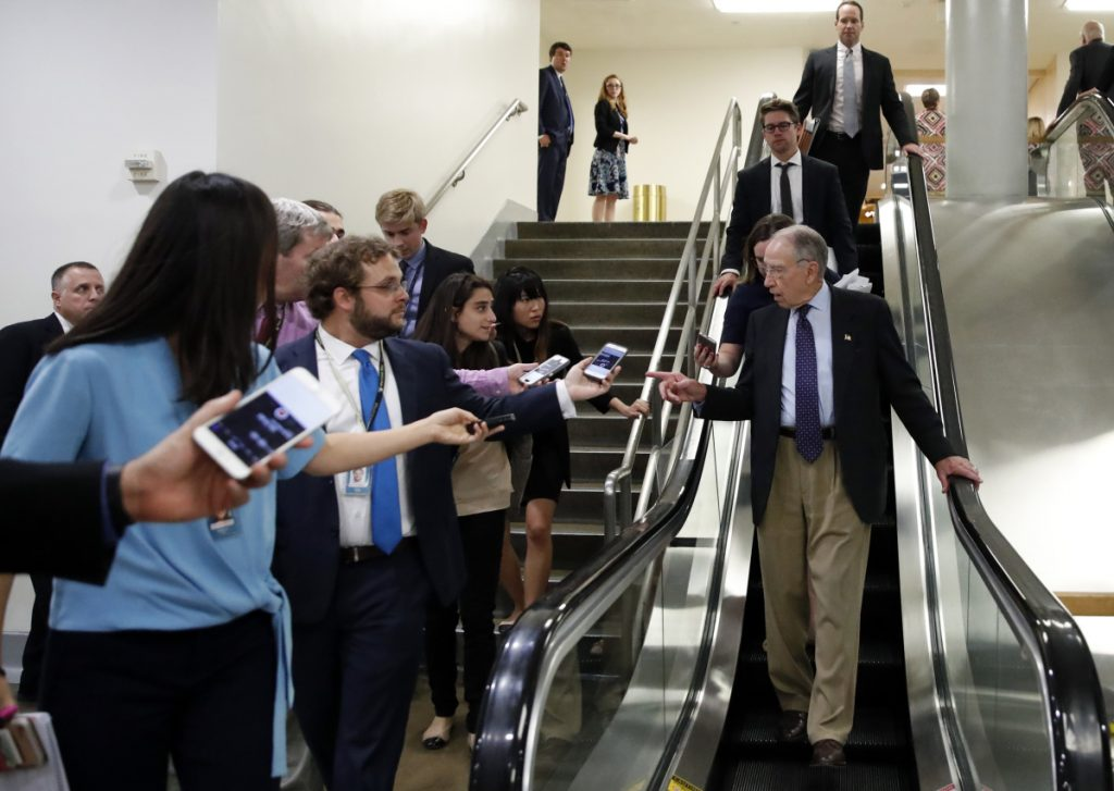 Senate Judiciary Committee Chairman Chuck Grassley, R-Iowa, talks with reporters as he uses the escalator on Capitol Hill on Wednesday in Washington.