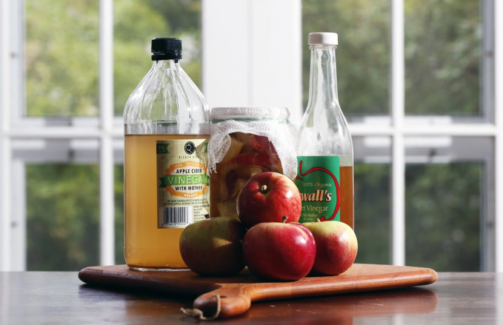 Maine apple vinegars made by Harry Ricker of Ricker Hill Orchards in Turner (left), and Bob Sewall of Sewall Orchard in Lincolnville (right) with a homemade vinegar brewing in a jar (center).