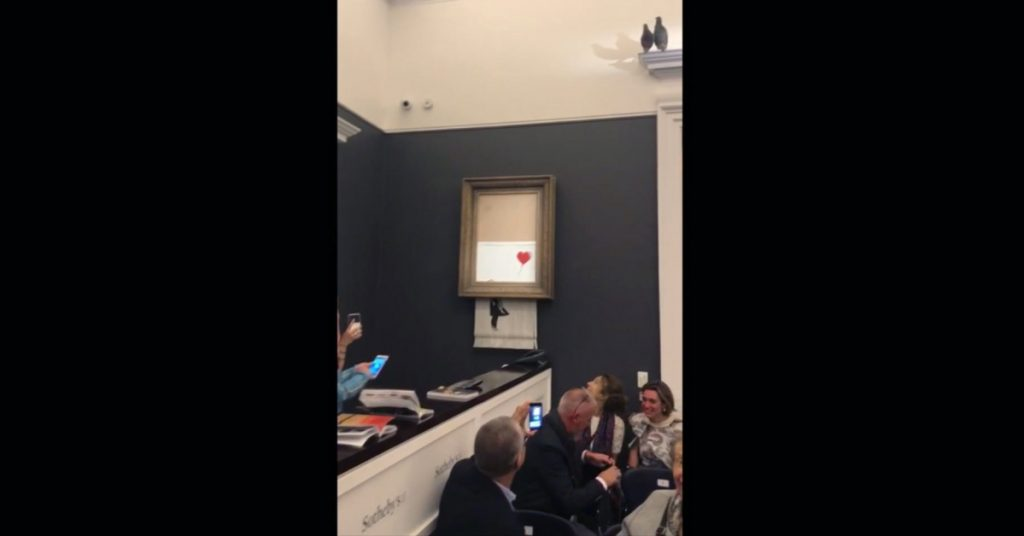 "In this screen grab taken from video Friday, people watch as the spray-painted canvas ""Girl With Balloon"" by Banksy is shredded at Sotheby's in London."