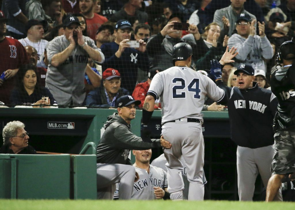 Gary Sanchez is greeted at the New York Yankees dugout after the first of his two home runs against the Boston Red Sox Saturday night at Fenway Park. (AP Photo/Elise Amendola)