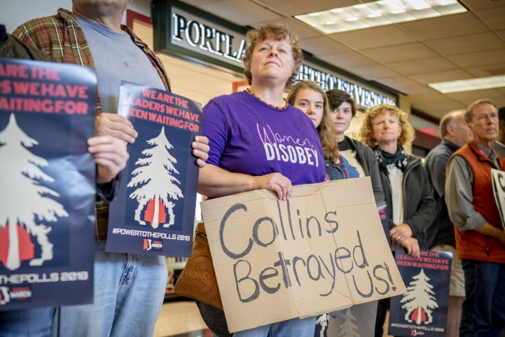 Cecelia Corey of Clinton holds a sign during a We Believe Survivors rally Sunday at the Portland International Jetport. About 50 people showed up at the noontime protest against Sen. Susan Collins.
