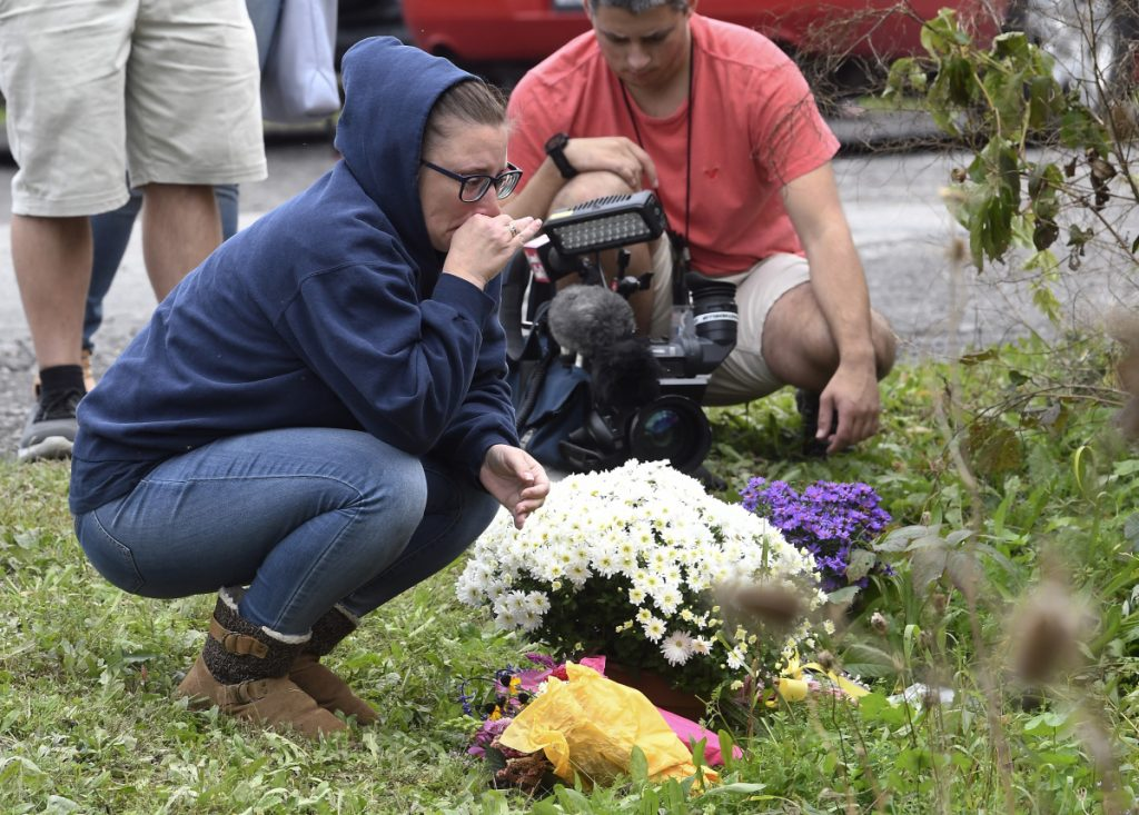 A woman kneels after placing flowers on Sunday at the scene where 20 people died when a limousine crashed into a parked SUV a day earlier in Schoharie, N.Y.