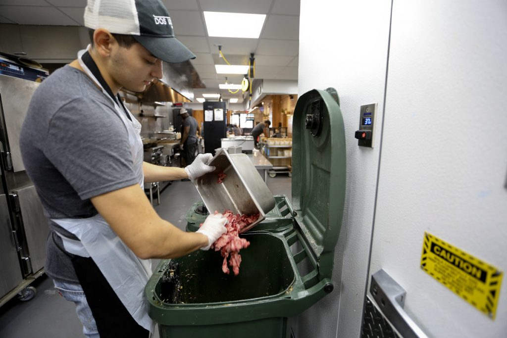 Konrad Navarrete, part of the kitchen crew at Dos Toros restaurant in New York, dumps meat scraps into the organics processing bin. New York City has begun requiring chain restaurants to separate their food waste from other trash.