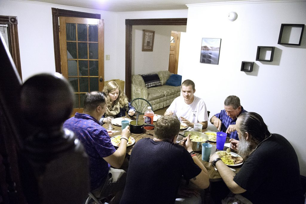 Jesse Harvey, back center, has dinner with residents of Journey House, a Lewiston home for men in recovery from substance abuse disorders. Harvey, the founder of Journey House, is in the process of opening a recovery house in Auburn for women.