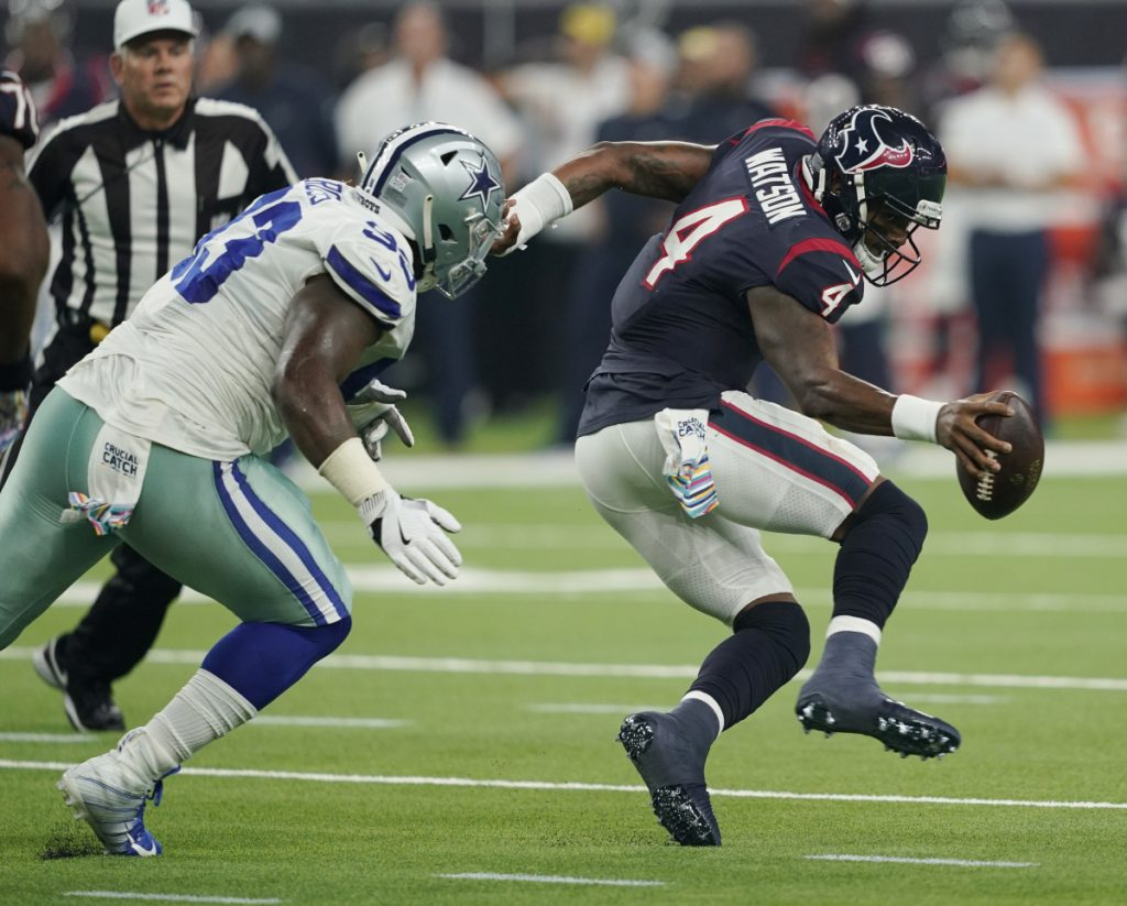 Houston quarterback Deshaun Watson is pressured by Dallas defensive tackle Daniel Ross on Sunday in Houston. The Texans beat the Cowboys, 19-16 in overtime.