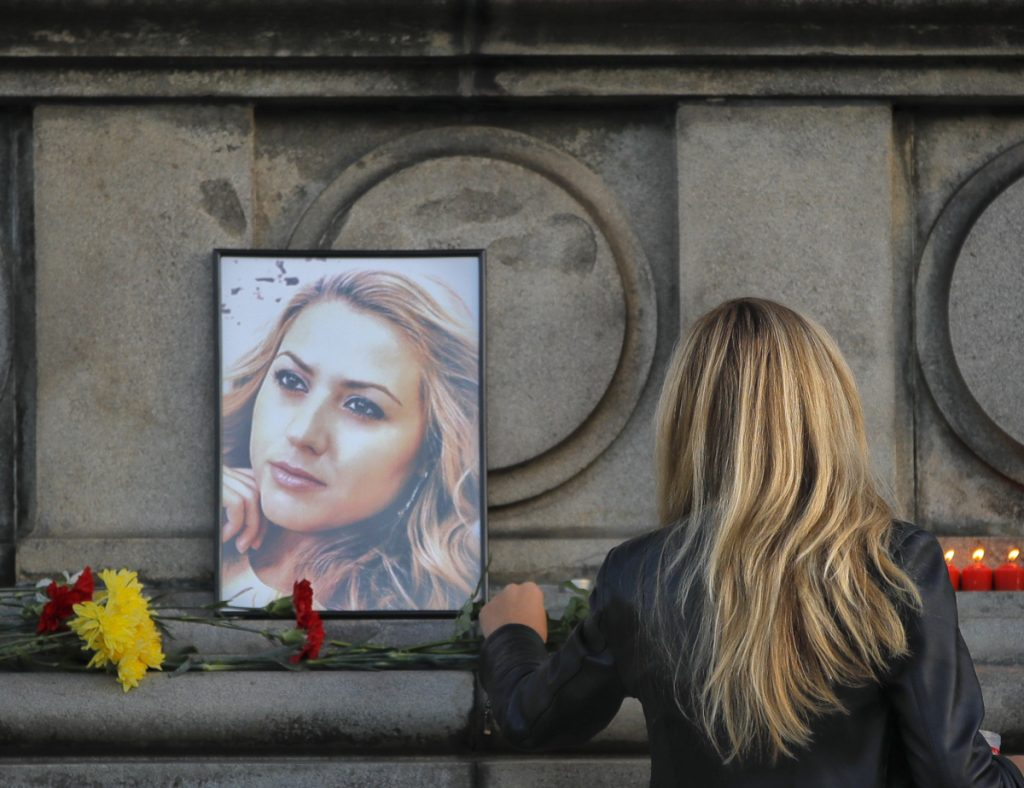 A woman places flowers next to a portrait of slain TV reporter Viktoria Marinova in Ruse, Bulgaria, Monday.