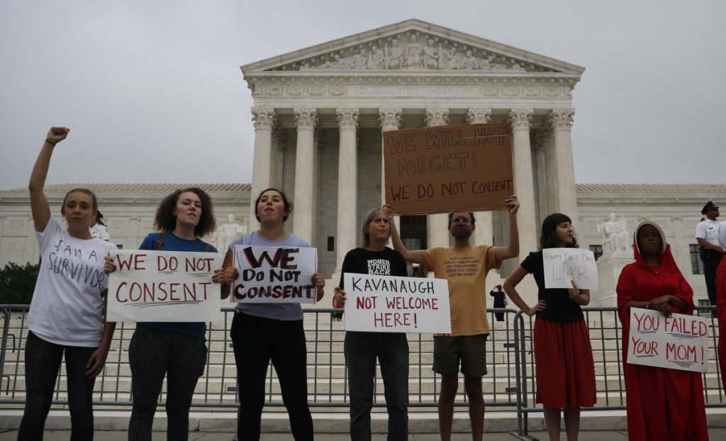 A small number of activists protest in front of the Supreme Court on Tuesday while Brett Kavanaugh is welcomed by his new colleagues. The court heard arguments over increased prison sentences for repeat offenders.