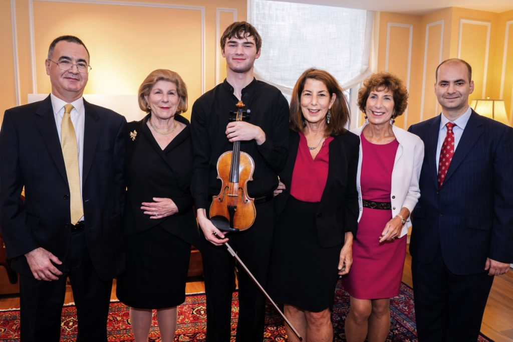 """In this photo provided by Chris Lee, Juilliard student Nathan Meltzer, center, poses with the """"Ames, Totenberg"""" Stradivari of 1734 violin loaned to him by the daughters of the late violinist Roman Totenberg, Tuesday, Oct. 9, 2018 in New York. From left are Bruno Price, of Rare Violins of New York, Nina Totenberg, Meltzer, Amy Totenberg, Jill Totenberg and Ziv Arazi or Rare Violins of New York. (Chris Lee via AP)"""