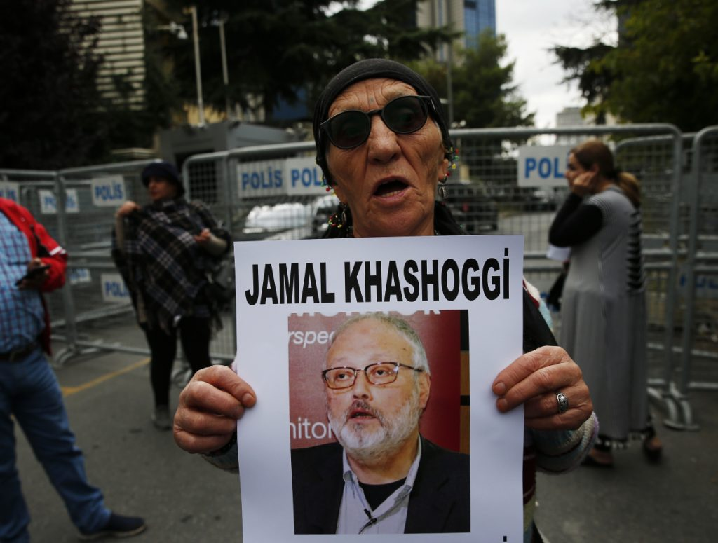 At left, a member of the Human Rights Association Istanbul branch, holds a poster with a photo of missing Saudi journalist Jamal Khashoggi, during a protest on Tuesday.