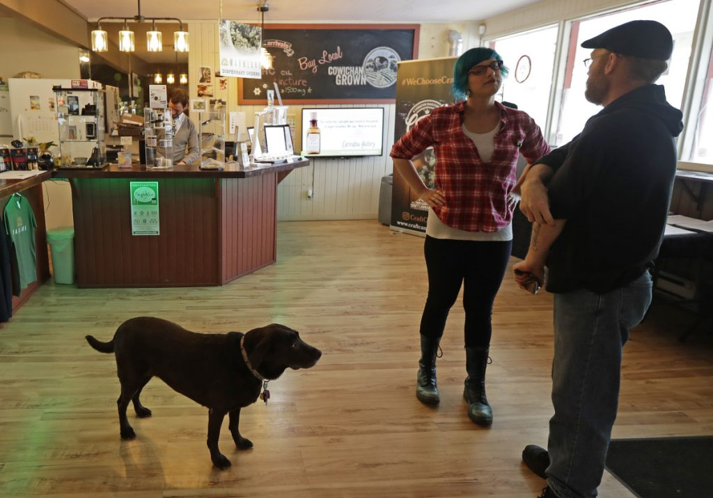 Customer Seth McKay, talks with manager Ruby Bressan, at the Warmland Centre, a medical marijuana dispensary in Mill Bay, British Columbia.