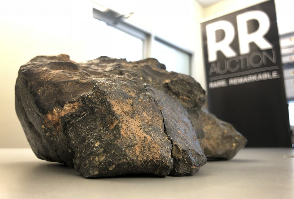 A lunar meteorite found in Northwest Africa last year rests on a table in Amherst, N.H. The rock could sell for $500,000 or more in an online auction that runs from Thursday until Oct. 18.