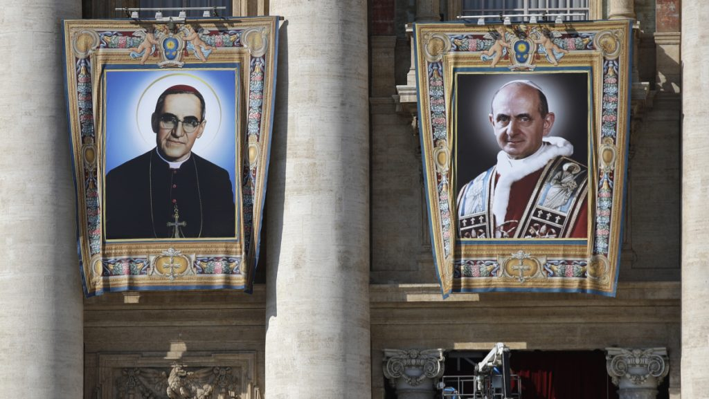 The tapestries of Roman Catholic Archbishop Oscar Romero, left, and Pope Paul VI hang from a balcony of the facade of St. Peter's Basilica at the Vatican. Pope Francis will elevate them to sainthood Sunday.