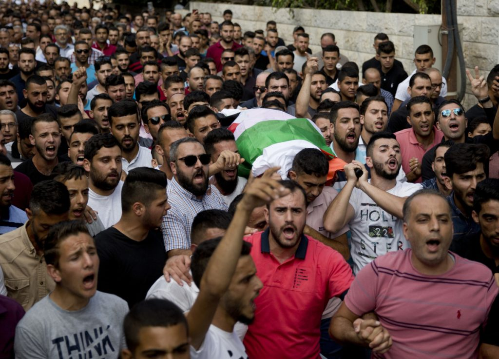 Palestinians carry the body of Aisha Rabi, 48, during her funeral in the West Bank village of Biddya on Saturday. Rabi was struck in the head by a stone thrown by Israeli settlers, Palestinians said.