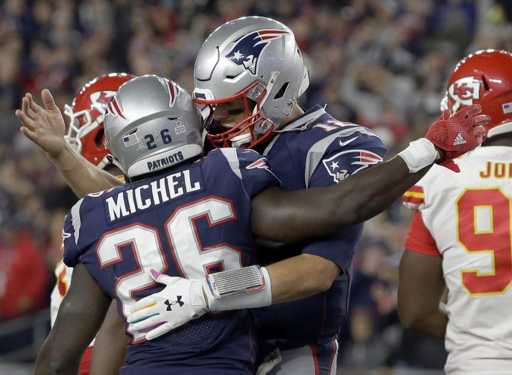 New England Patriots quarterback Tom Brady, right, celebrates a rushing touchdown by running back Sony Michel in the first half Sunday night. The Patriots beat the Chiefs, 43-40.