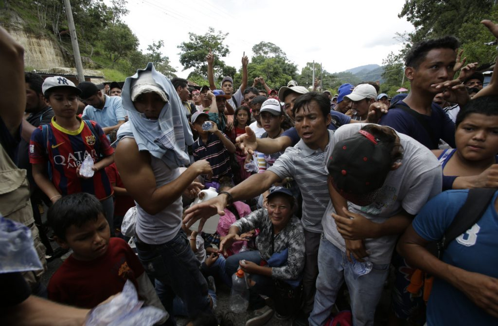 Honduran migrants receive water from Guatemalan police at the Honduran border crossing Monday. An estimated 1,600 migrants traveling together eventually crossed into Guatemala as they head for the United States.
