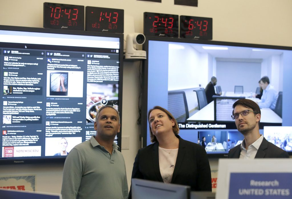 Samidh Chakrabarti, Director of Elections and Civic Engagement, from left, stands with Katie Harbath, Global Politics and Government Outreach Director and Nathaniel Gleicher, Head of Cybersecurity Policy, during a demonstration in the war room, where Facebook monitors election related content on the platform, in Menlo Park, Calif., Wednesday, Oct. 17, 2018.