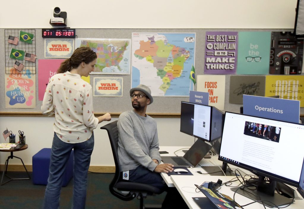 Lexi Sturdy, election war room lead, left, talks with researcher Andre Souza during a demonstration in the war room, where Facebook monitors election related content on the platform, in Menlo Park, Calif., Wednesday, Oct. 17, 2018.