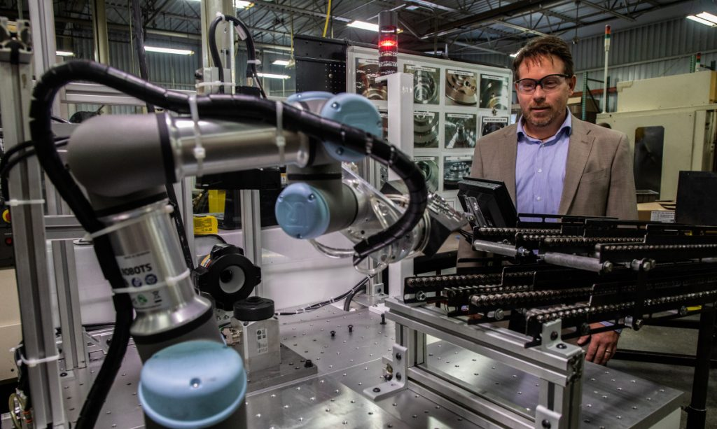 Brian Pelke, president of Kay Manufacturing, an automotive parts company in Calumet City, Ill., shows off the company's newest collaborative robots, or cobots. Pelke said he expects his new cobots to give him an additional competitive edge, and that he has never laid anyone off as a result of automation.